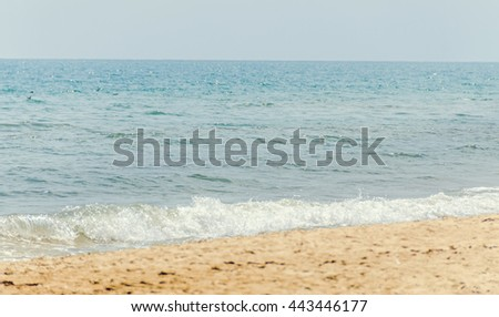 The Black Sea shore from Albena, Bulgaria, beach with gold sands, blue sea water, waves and clouds sky.