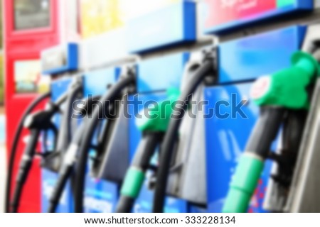 The blurry photo of fuel filling up hose and nozzel at gas station represent the british petroleum business concept related idea.