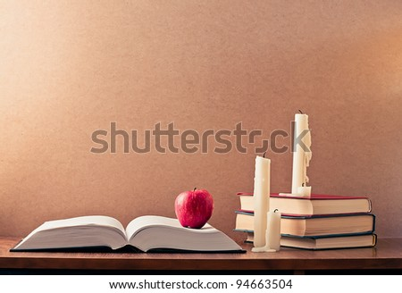 The book, red apple and three candles - stock photo