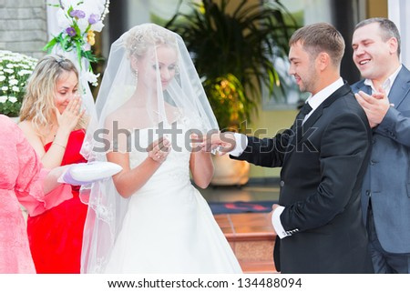 The bride puts on to the groom a finger a ring while thefriends standing in the background - stock photo
