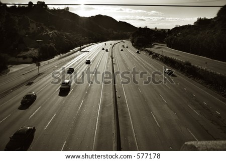 The CA 101 highway in the Hollywood Hills. Taken against the sun, asphalt reflecting light. A ridiculous number of lanes visible. - stock photo
