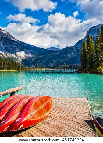 The concept of active tourism and vacation. Emerald Lake in the Canadian Rockies. Shiny red kayaks are dried upside down - stock photo
