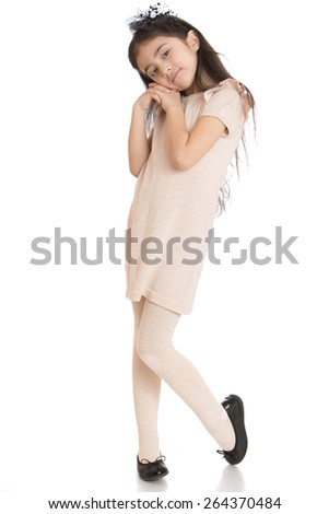 The dark-haired girl posing while standing in a beige dress - isolated on white background - stock photo
