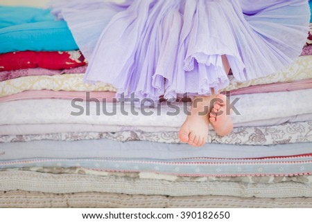 "The fairy tale ""the princess on a pea"". Little girl in lilac tatu skirt sitting on the high bed. Bare foot if the girl. Legs of a little girl sitting on a pile of colorful mattresses.  - stock photo"