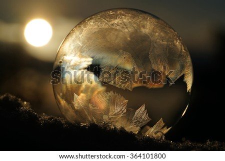 The freezing soap bubble on the snow with the sun