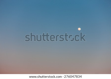 The Full Moon in daylight blue sky - stock photo
