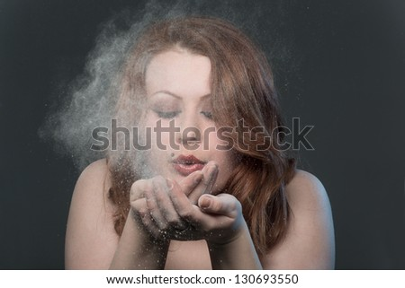 The girl blows off a dust from a palm - stock photo
