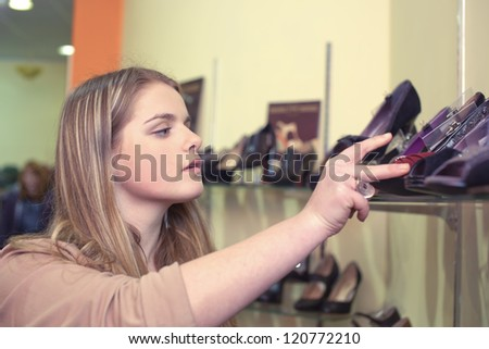 The girl chooses shoes - stock photo
