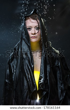 The girl in a black cape under drops - stock photo