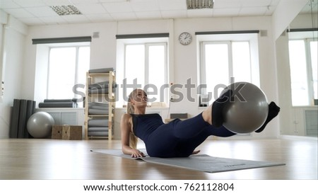 the girl shows the Pilates exercise. A girl in black clothes shows a Pilates exercise in the gym.