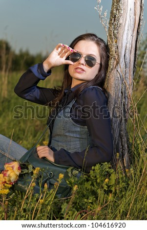 The girl sits in sunglasses, at a tree