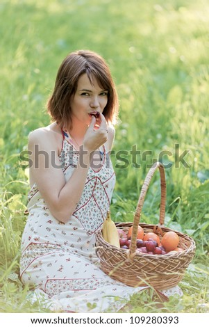 The girl sits on a glade and eats a sweet cherry