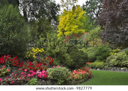 The green lawn surrounded by flower beds and blossoming trees - stock photo