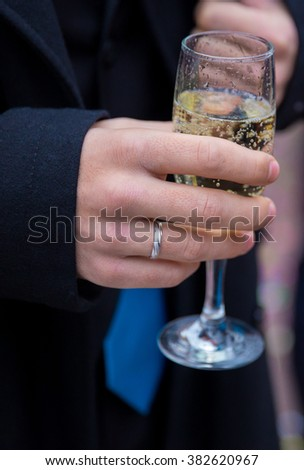 The groom's hand with a glass of wine