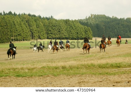 The group of horsemen riding on a field.
