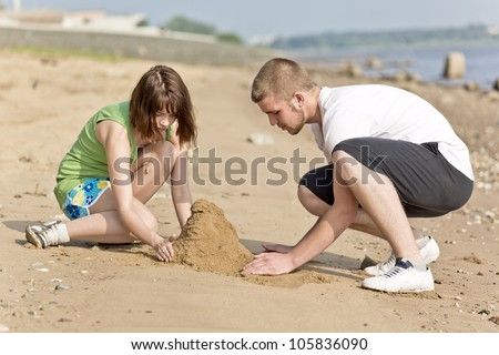 The guy and the girl fill a heap of sand - stock photo