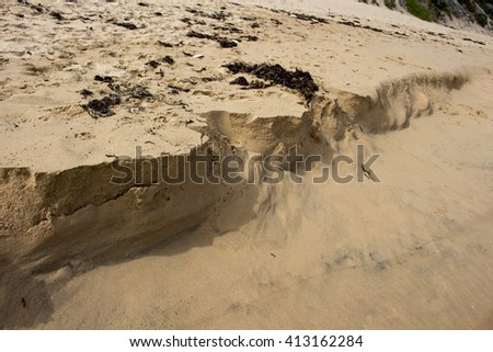 The Indian Ocean waves at Dallyellup Beach near Bunbury South Western Australia are washing the  crumbling sand formations   away as the tide comes in . - stock photo