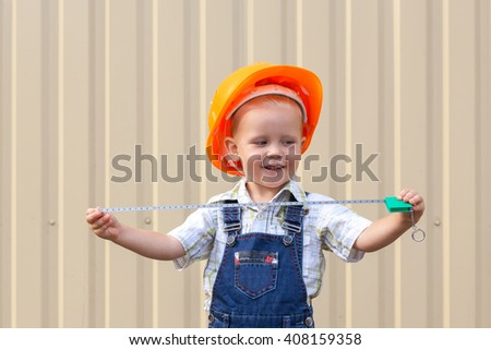 The Little boy in the helmet of the builder. - stock photo