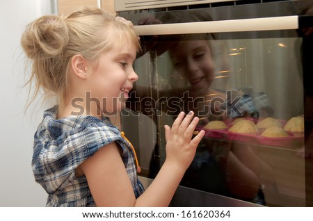 The little girl looks at a tasty fruitcake in the oven - stock photo