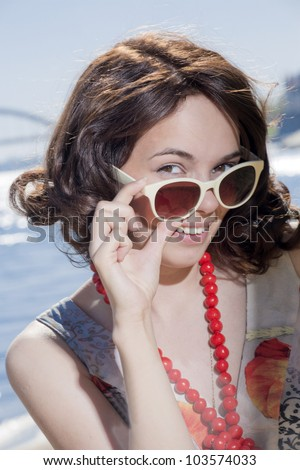 The lovely girl looks over sun glasses