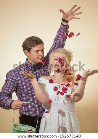 The man throws petals of roses on the girl - stock photo
