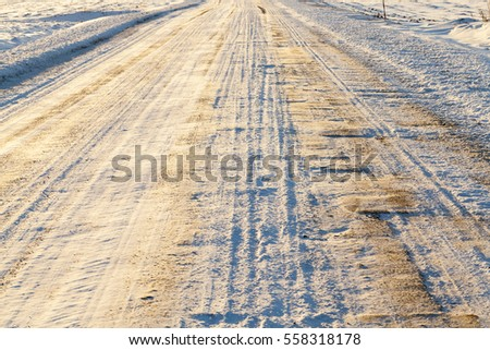 the marks of a car left on the paved road. The photo was taken closeup, small depth of field. The winter season, snow from the car became dirty.
