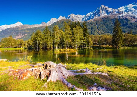 The mountain resort of Chamonix, Haute-Savoie. City Park is illuminated by sunset. The lake reflected the snow-capped Alps and evergreen spruce - stock photo