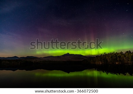 """The Northern Lights"" over Lake Chocorua in New Hampshire.  Vibrant, dancing green light behind Mt. Chocura while a hint of purple rises into the northern sky."