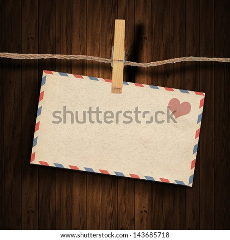 the old envelope and clothes peg wood background - stock photo