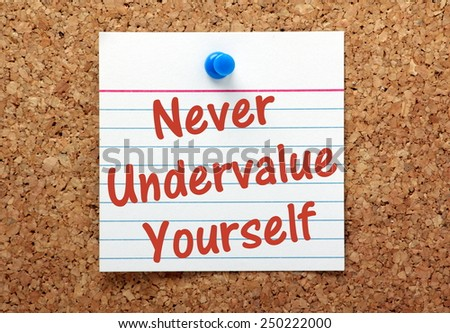 The phrase Never Undervalue Yourself written on an index card and pinned to a cork noticeboard as a reminder - stock photo