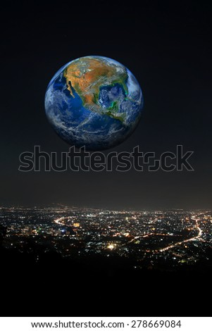 the planet over the city at night, including elements furnished by NASA - stock photo