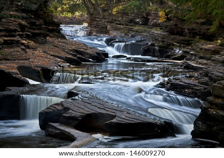 The Presque Isle River winds through the Porcupine Mountains Wilderness State Park in Michigan's Upper Peninsula. - stock photo