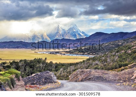 The road between turned yellow hills and river goes to snow-covered black rocks. Patagonia. Vertiginous landscape in the Chilean Andes - stock photo