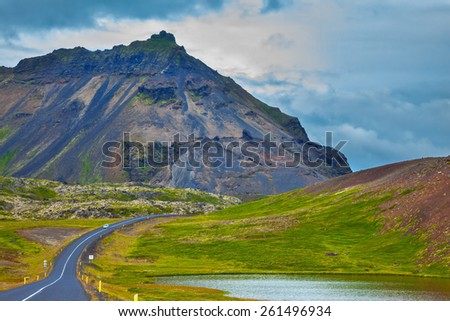 The road passes through the picturesque landscape in the mountains and lakes. Cloud Iceland in the summer - stock photo