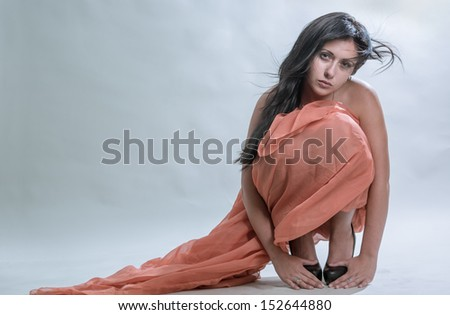 The sad girl sits on a grey background - stock photo