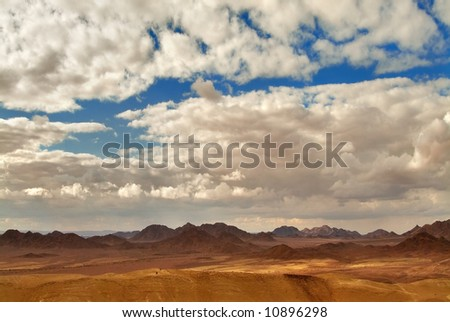 The sun and clouds above mountains of desert Sinai - stock photo