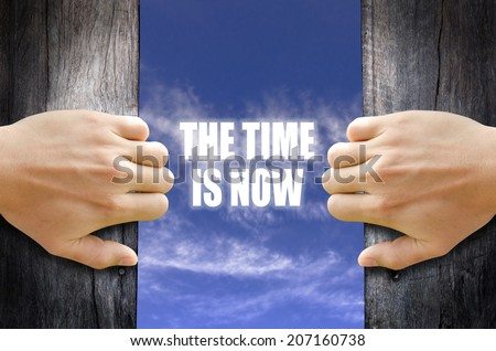 """""""The time is now"""" text in the sky behind 2 hands opening the wooden door. - stock photo"""
