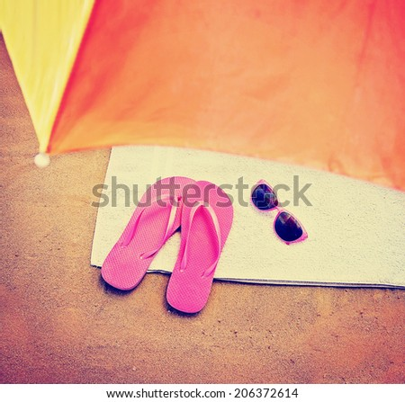 the top of an umbrella and pink flip flop sandals and sunglasses toned with a retro vintage instagram filter  - stock photo