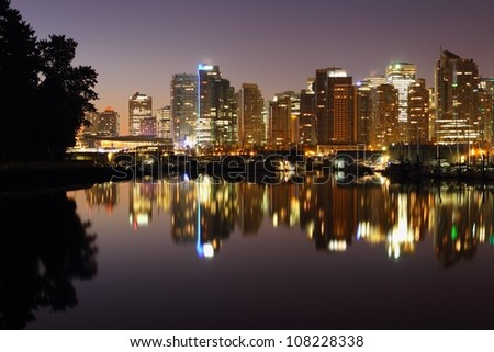 The towers of Downtown Vancouver reflect in the calm water of Coal Harbor at twilight. The trees of Stanley Park frame the left side. British Columbia, Canada. - stock photo