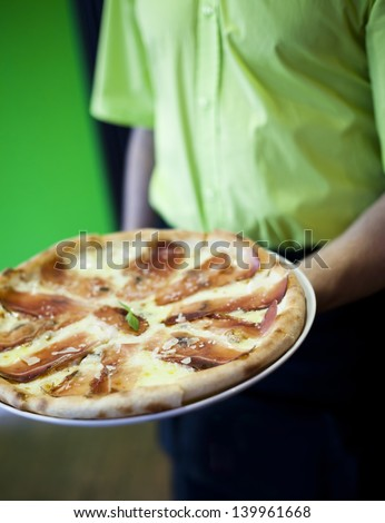 The waiter of restaurant with a pizza in hands - stock photo