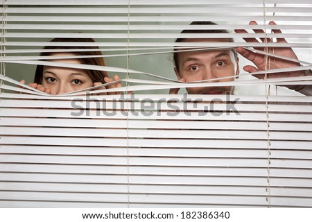 The woman and the man looks through jalousie - stock photo