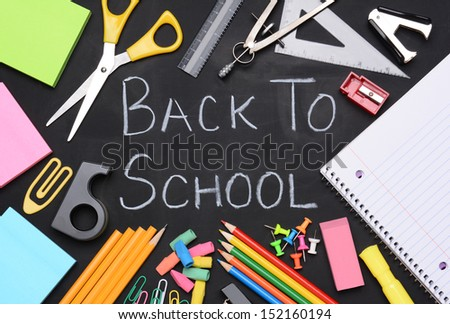The words Back to School written on a chalkboard surrounded by school supplies including, paper, scissors, pencils, erasers, paper clips, compass, ruler, push pins and more. - stock photo