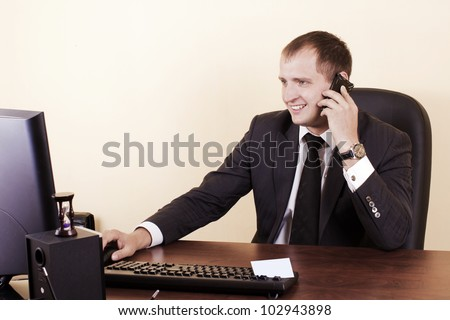 The young businessman speaks by phone on a workplace
