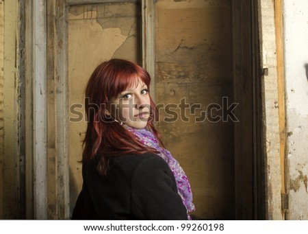 The young girl costs at the hammered window - stock photo