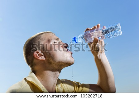 The young man pours water from a bottle