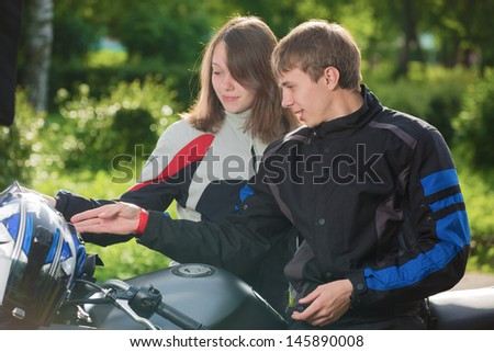 The young man shows girls a motorcycle