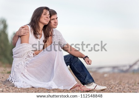 The young pair sits on a beach - stock photo