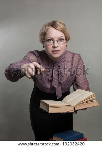 The young woman holds the book and specifies a finger - stock photo
