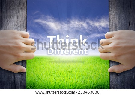 """Think Difference"" Motivational quotes. Hands opening a wooden door then found a texts floating among new world as green grass field, Blue sky and the Sunrise. - stock photo"