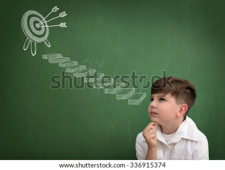 Thinking schoolboy with goal at top of the stairs drawing on blackboard - stock photo